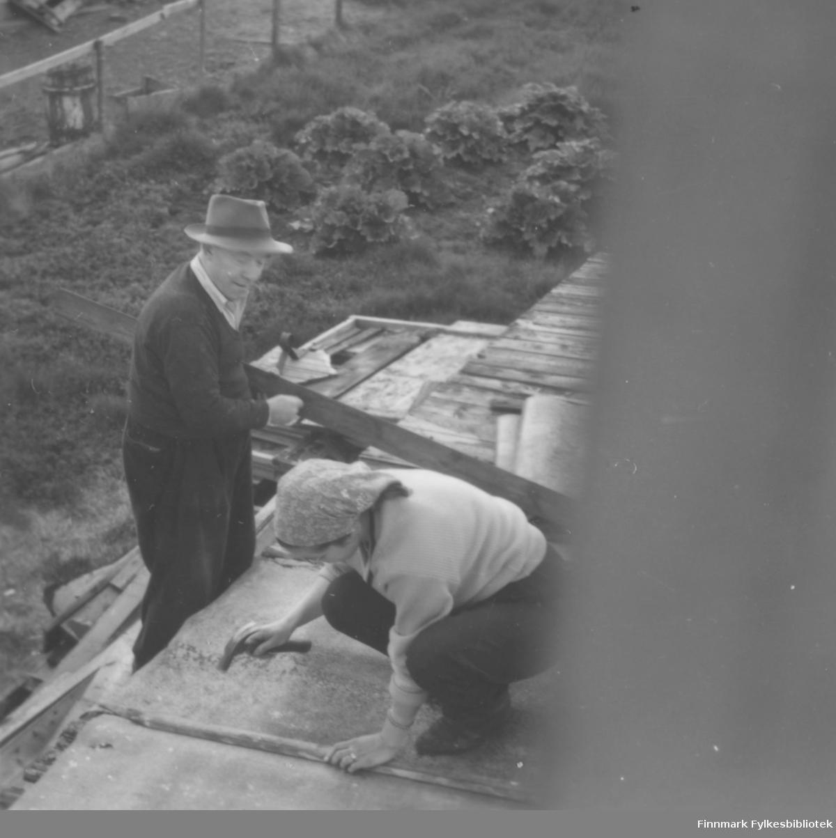 Takreparasjon på sjåtaket i Slettengata hos familien Kvam, ca. 1955-1960. Bjørg Hedberg snekrer, mens hennes far, Halfdan Kvam, rekker henne mer materiale