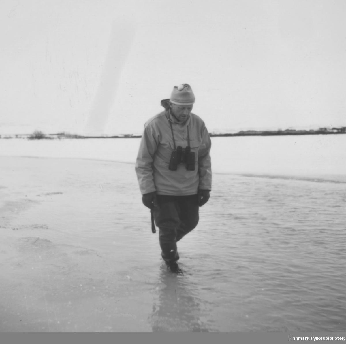 Fritz Ebeltoft vasser langs en strand, kanskje i Komagvær? Han er godt kledd, og det ser ut til å være snø i landskapet bak ham. Raundt halsen har han en kikkert. Bildet er antakelig tatt om våren, ca. 1960-1965?