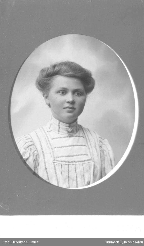 Portrett av ukjent kvinne. Kvinnen er kledd i lys, stripete overdel og har en brosje festet i halslinningen. Bildet er trolig tatt på begynnelsen av 1900-tallet.