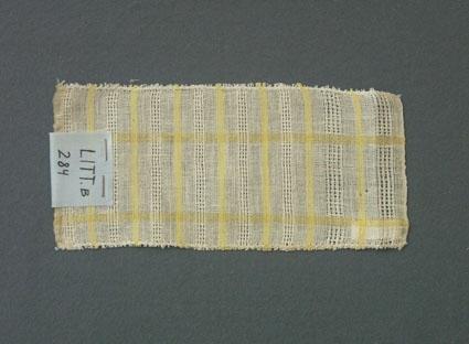 Prov till gardin vävd i tuskaft och stramaljbindning. Provet har bomullsgarn i varp och lingarn i inslag.Ytterligare prov och vissa vävuppgifter finns i pärm gardiner A, litt B 284 B.