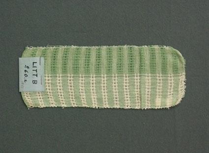 Två prov i ett, prov till gardin vävd i tuskaft och stramaljbindning. Provet har bomullsgarn i varp och inslag.Ytterligare prov och vissa vävuppgifter finns i pärm gardiner A, litt B 260 a.