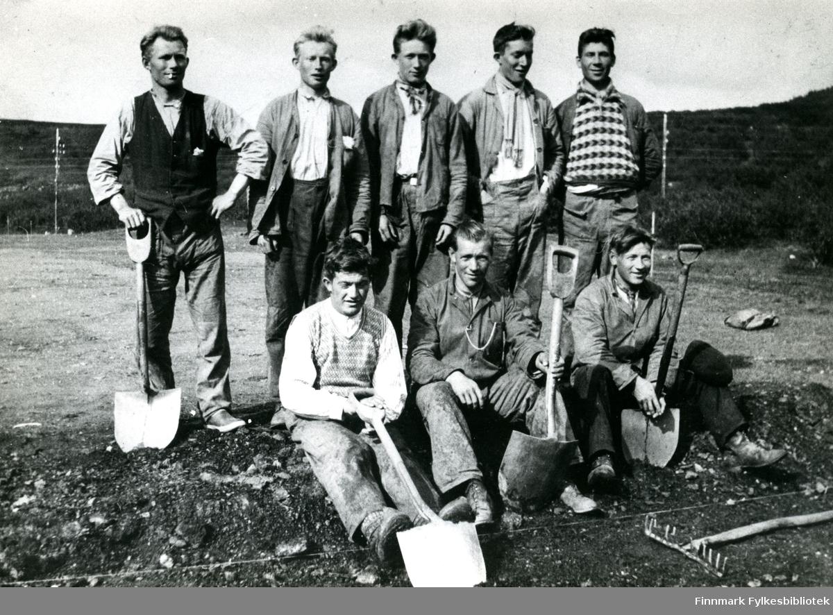 Bildet viser åtte unge menn, poserende med spader.