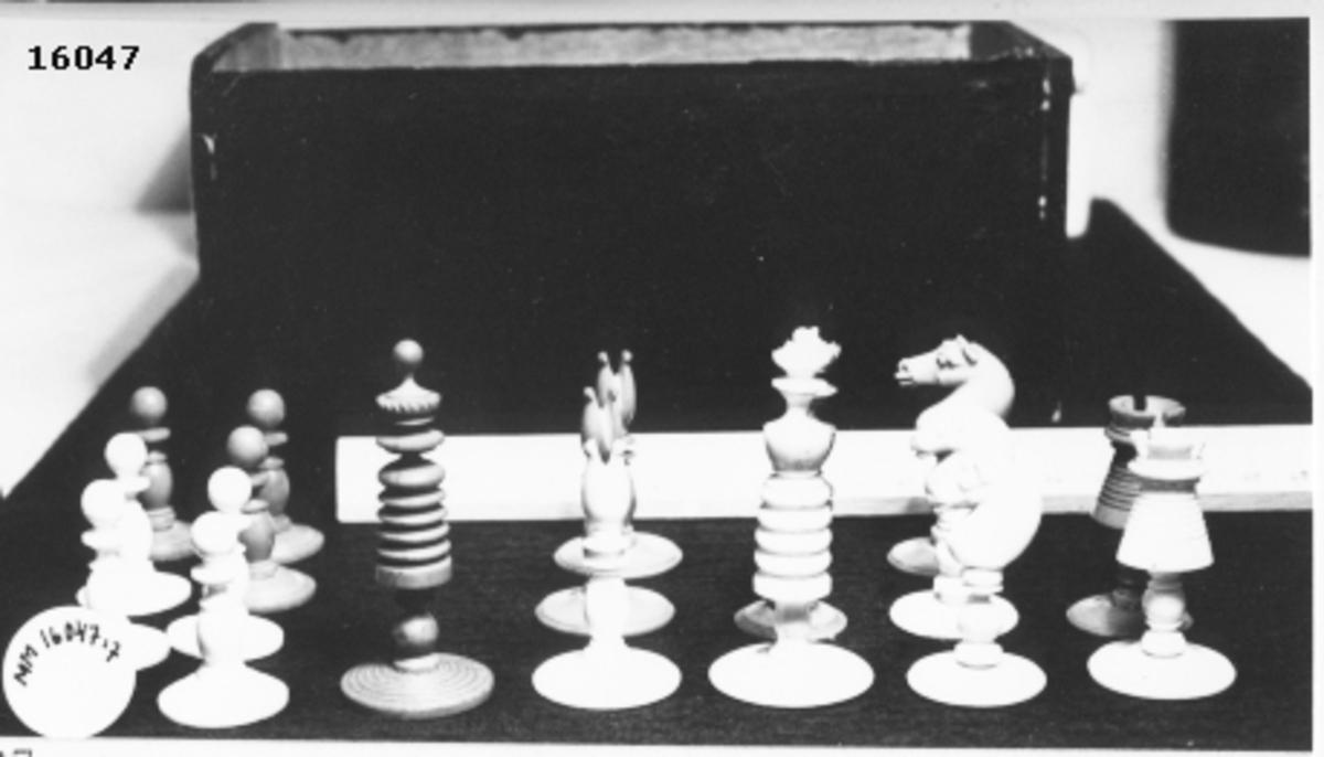 Utskuren schackpjäs, vit bonde, som står på cirkelrund fot.
