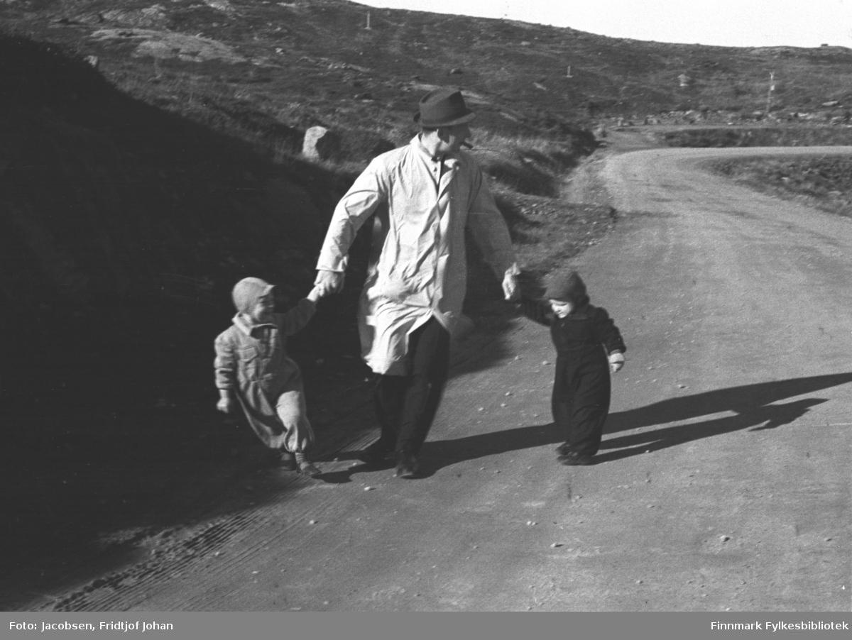 Ragnvald Jacobsen på tur med sønnen Ivar og nevøen Arne. Ragnvald er iført en lys frakk, mørke bukser og sko med en ganske mørk hatt på hodet. Han leier de to barna i hver sin hånd. Gutten til høyre på bildet er Ivar. Han har en helt mørk buksedress og litt lysere lue på seg. Til venstre på bildet er Arne. Han har en ganske lys buksedress og lue på seg. Veien de går på er grusdekt. Den er idag Rv 94 og går ned fra Storsvingen mot Rypefjord. Terrenget bak dem er stort sett lyngdekt med en del stein liggende rundt. Toppen bakerst på bildet er Storsvingen og til høyre, utenfor bildet, ligger Jansvannet. Formiddagssola kaster skygge av de tre på veien en sensommerdag/tidlig høstdag.