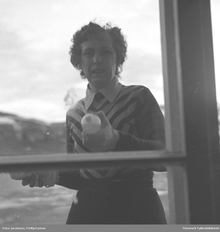 Karen Trondsen (Dalbom), fotografert i Nedre Grønnevoldsgate (i dag Strandgt.), i Hammerfest sentrum før 1940. Det er en fin vinterdag med sol, og fotografens skygge er synlig nede i høyre hjørne av bildet