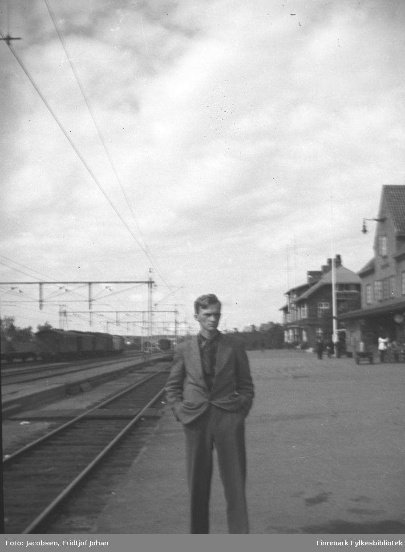 Fridtjof Johan Jacobsen står på en togstasjon/perrong. Han har en ganske mørk dress på seg. Togskinner og el-linjer samt et tog ses til venstre på bildet. Til høyre står to store bygninger, en stolpe og noen mennesker. Bildet kan være tatt i Hamar eller på Lillehammer.