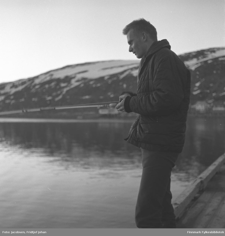 Arne Jacobsen prøver fiskelykken på Hauankaia i Hammerfest. Han har en mørk boblejakke og mørk bukse på seg og har en fiskestang i hendene. Hammerfest havn har blikkstille sjø og i bakgrunnen ses bebyggelsen langs Fuglenesveien noe diffust. En del snøflekker ligger enda på Fuglenesfjell, noe som tyder på at bildet er tatt om våren.