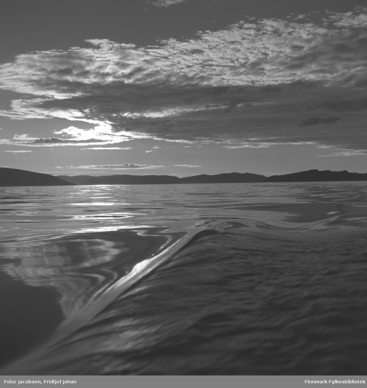 Kveldsstemning med en blikkstille sjø utenfor Hammerfest/Rypefjord. Kjølvannet etter en båt ses på sjøen og øya Håja ses helt til venstre på bildet. Det lange fjellpartiet som ligger i horisonten er Sørøya. Et større skyparti som svever inn fra nord skygger over kveldssola, men ellers flott sommervær.