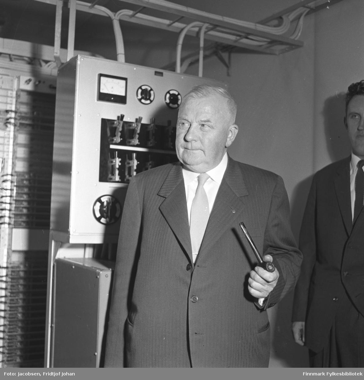 Dette er fra da Bossekop (Alta) - og Elvebakken sentraler ble automatisert. Telegrafdirektør Leif Larsen. Han er iført en mørk dress med hvit skjorte og lyst slips og holder en pipe i hånda. Bak han står Rolf Køste. Rolf Køste var da telegrafbestyrer i Mehamn. Også han har en mørk dress, hvit skjorte og slips på seg. Noe utstyr står langs veggen bak dem og mye ledninger går langs taket.