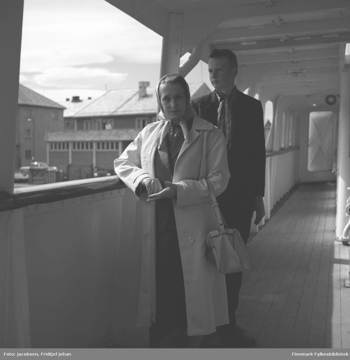Aase og Arne Jacobsen ombord i Hurtigruta ved Hammerfest havn. I bakgrunnen ligger Hammerfest tollstasjon