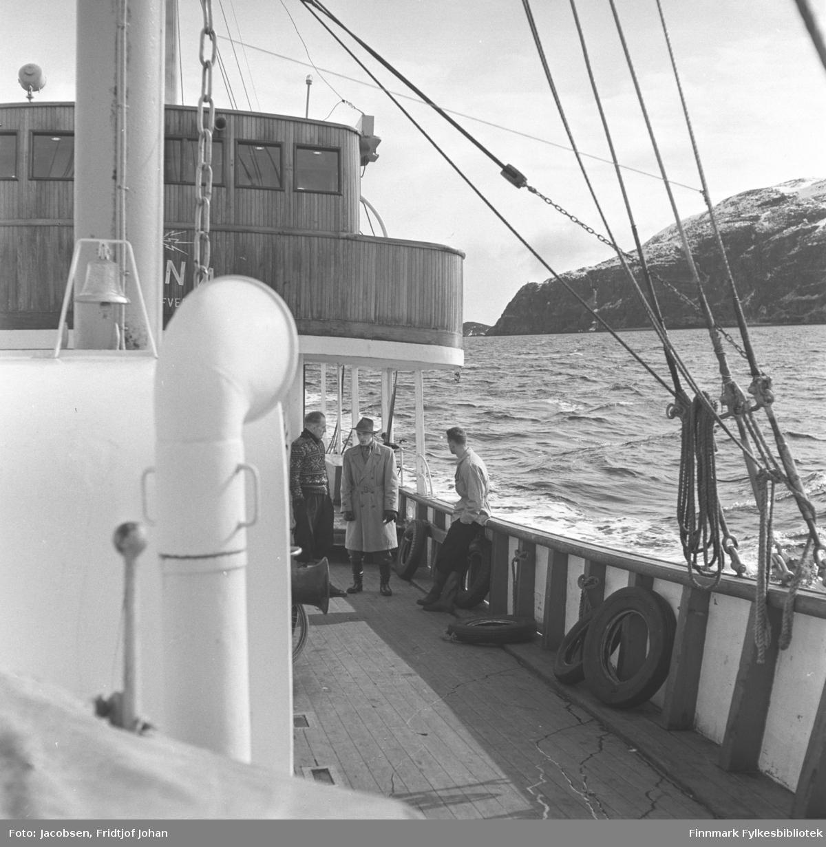 """Telegrafverkets båt M/S """"Tana"""" var stasjonert i Hammerfest, her er den ute på havet. Tre menn står ved båtrekka."""