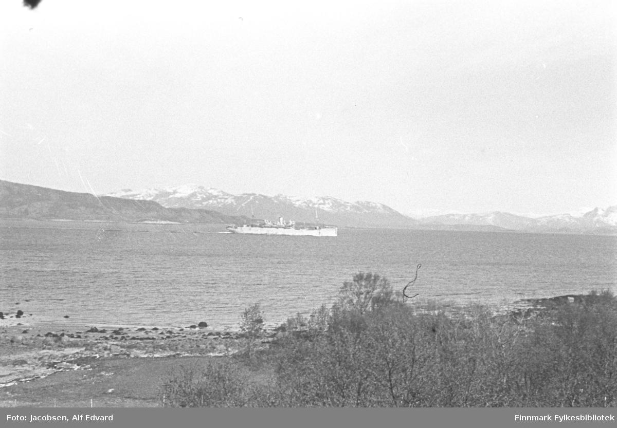 Et fartøy fotografert på ganske lang avstand. Skipet er lyst med et ganske lavt overbygg. Små bølger på sjøen tyder på rolige vindforhold. På andre siden av fjorden går fjell langs hele bildet. Det er snøflekker på de øverste toppene. Nærmest kamera er en strandkant. En liten elv/bekk renner ned i sjøen til venstre på bildet. Noen små trær og busker foran på bildet og lengst til høyre på bildet ses flomålet med tang på steinene. Bildet er sannsynligvis tatt i Lødingen våren 1945.