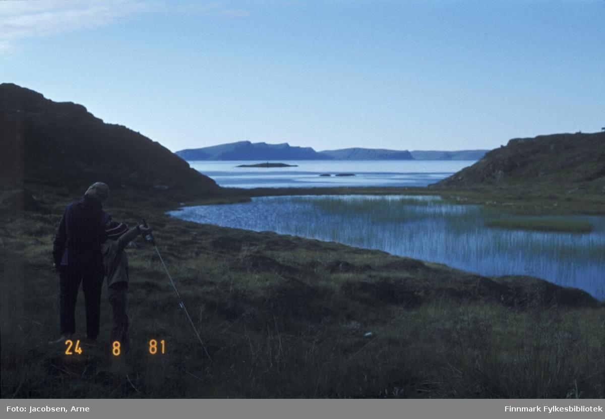 Fra Fjordadalen i Rypefjord. Aase Jacobsen og Tor Jørgen på tur. Han har en fiskestang i handa og lue på hodet. Et lite vann med en del siv i midt på bildet. Gress og lyng på bakken i forkant og på sidene av vannet. To små fjellknauser på hver side i bildet danner en ramme rundt Sørøysundet. Rypklubbskjæret midt på bildet med Småskjæran til høyre foran det. Helt i bakgrunnen ses Sørøya med Skippernestinden, Høgnova og Borvikklubben ovenfor skjærene.