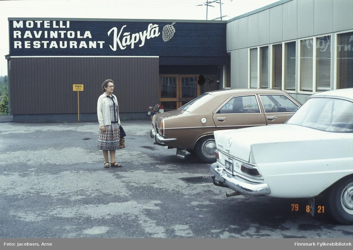 Aase Jacobsen på ferietur i Finland. Hun står utenfor Käpylä motell i Keminmaa. Hun har åpne klikk-klakk'er mønstret skjørt, lys jakke og flerfarget bluse på seg. I handa holder hun en veske. På den asfalterte parkeringsplassen står det også et par biler parkert, den nærmeste en lys Mercedes. Den andre, en Chrysler, er nok deres ettersom det finnes flere bilder av den med de utenfor. Det står en krukke med blomster ved siden av inngangen og et lite, firkantet skilt står midt på veggen. Persienner er trukket for alle vinduene på veggen til høyre.