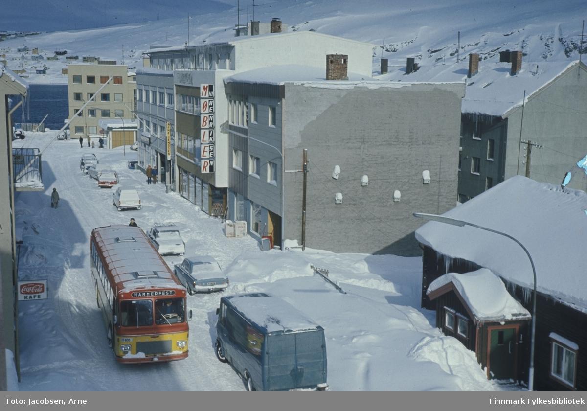 Storgata i Hammerfest sentrum en vinterdag. Solskinn og pent vær, men mye snø i gata og i terrenget. En FFR-buss og en varebil møtes i gata utenfor Nissenhytta til høyre og Larsens cafe, på folkmunnet kalt Sjårra, til venstre. Biler står parkert langs fortauet foran Arne Jenssen-bygget og Henriksen møbler. I enden av gata ligger drosjesentralen og det store bygget bak den er FFRs hovedadministrasjon. Oppe til venstre kan man se en liten del av bydelen Fuglenes.