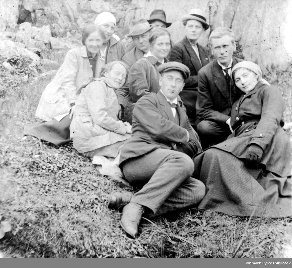 Fotografi av en gruppe mennesker som sitter i gresset nedenfor en fjellskråning. Kvinnen foran til venstre er sannsynligvis lærerinne Julie Jacobsen fra Vardø. Hun var datter til smedmester i Vardø Ole Sigfrid Jacobsen og hustru Anna Christine Vibe Jacobsen. Det er fire andre kvinner og fem menn på bildet. De er ukjente.
