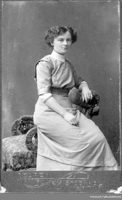 Portrett av ei ukjent kvinne som sitter på armlenet til en stol. Hun er kledt i en lys kjole