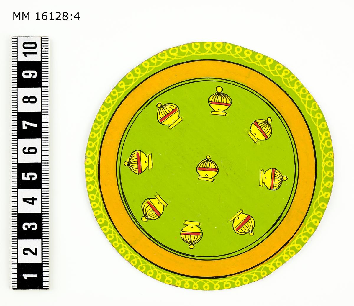 Indiska spelkort av cirkelrunda plattor av styv kartong med bemålad framsida  och orange baksida. :4 Ljusgrön botten med från mitten: 9 lökkupoler samt i cirkel: 2 svarta, 1 orange, 1 svart linje samt gul mönsterbård.