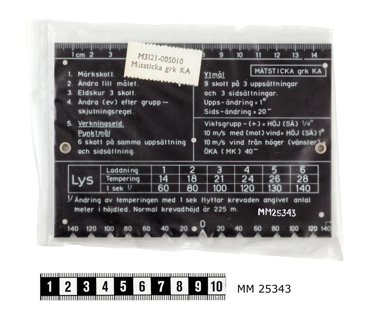 """Grön plastbricka med rektangulär form. Stansade hål med förstärkta kanter i varje kortsida. Ena långsidan rak med linjal i centimeter, motsatt sida har hack för mätningar med jämna mellanrum. Tryckt på de flata ytorna är olika minnesregler och dylikt som används vid eldledning av granatkastare. Där finns också en streckskala för mätningar i nämnda hack.  Mätstickan är förpackad i en plastpåse som har förslutits genom att två av sidorna har smälts samman. I plastpåsen ligger också en vit lapp med texten: """"M3121-005010 Mätsticka gkr KA""""."""