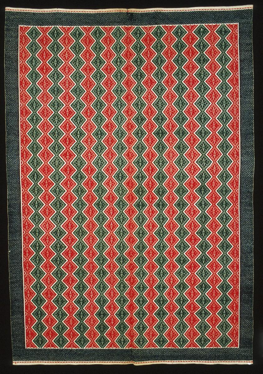 """Täcke vävt i opphämta. Täcket kan också ha använts som bordtäcke/duk. Yttäckande mönster av snedställda rutor som bildar röda och gröna ränder. Mörkblå bård runt om. Mönster i ullgarn på tuskaftsbotten i halvblekt lingarn. Täcket är ihopsytt på mitten av två delar, med efterstygn sydda med lintråd. Fållat i kortsidorna med 4 mm bred fåll. Stadkanter i långsidorna. Avslutat i kortsidorna med en smal mönsterrand i rött på linnebotten. Märkt med ett litet """"K"""" i korsstygn i ena kortsidan intill mittsömmen.Varp i 1-trådigt z-spunnet lingarn, 16 trådar/cm.Botteninslag i 1-trådigt lingarn.Mönsterinslag i 2-trådigt z-tvinnat ullgarn.Märkt på baksidan med påsydd tyglapp med texten: """"N° 143 a Torna h:d"""".Märkt med fastnästat bomullsband med texten: """"8356 MAL. SÄKR. 6/10""""."""