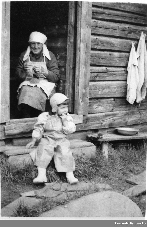 Margit N. Hølto med bundingen i buadøra på Høltostølen i Hemsedal i 1952.