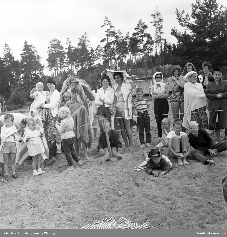 Det ser kallt ut då sommarens simskola vid Fläsian har avslutning. Mannen med megafonen på första bilden är Karl Henrik Rönström, badmästare, polis och senare idrottsintendent i Sundsvall.