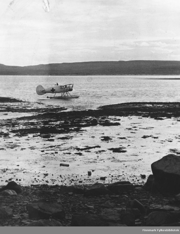 Ambulansefly/sjøfly fotografert i sjøkanten ved Nyborg. Flyet er en Waco LN-EAO som ble brukt av Norges Røde Kors til ambulanseflyginger i Nord-Norge sommeren og høsten 1940. Samme fly som på 97056-005.  I bakgrunnen ser vi Vesterelvneset.