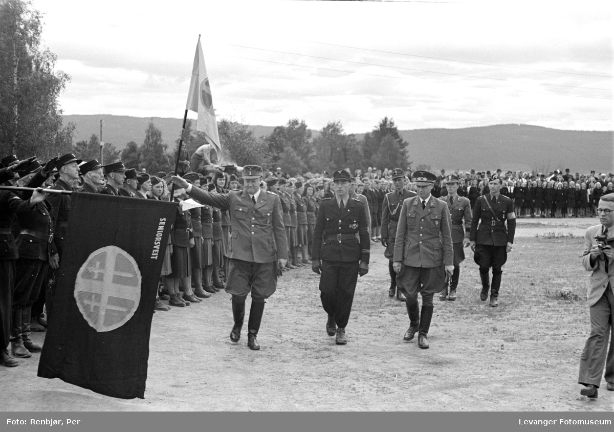 Fra Nasjonal Samlings stevne på Stiklestad. Hirden står oppmasjert med flagg, merket seniorsveit og solkorset.