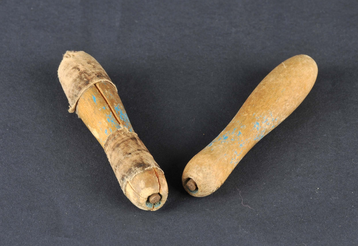 Handtak til hoppetau. Sjølve tauet har vore av gummi og har smuldra vekk. Det eine handtaket har sprukke og er reparert med tjøreband. Restar etter måling.