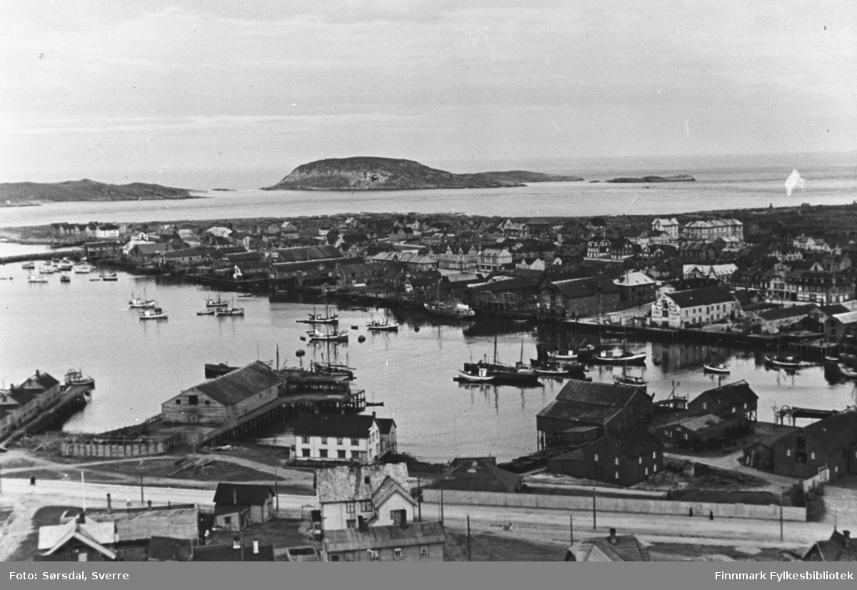 Flyfoto over Vardø i 1936. Havna med fiskebåter. I bakgrunnen ses Reinøya? Sjåer og hus ses også godt.