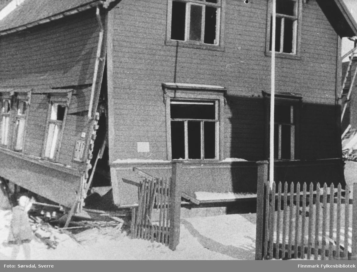 Bildet av huset til Holte som var det første huset som ble skadet i bombing i 1940/41. Ved siden av huset sitter en jente på huk.