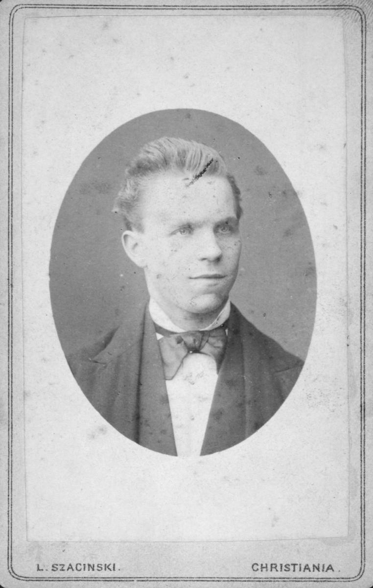 Portrett av en ung mann. Mannen har på seg dress og sløyfe rundt halsen. Det er ukjent hvem han er. Bildet kan være tatt på 1860-tallet, men dette er noe usikkert. Det er likevel tatt mellom 1850-1894.