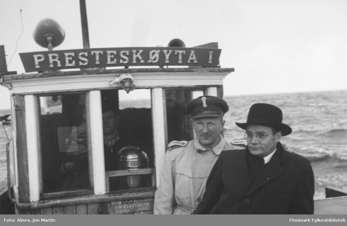 Presten på tur til yttersoknet i Loppa med 'Presteskøyta I', 1954. Offiseren er ukjent, til høyre for ham sogneprest Einar Bjorvand. I styrehuset skimter vi Alf Johannessen