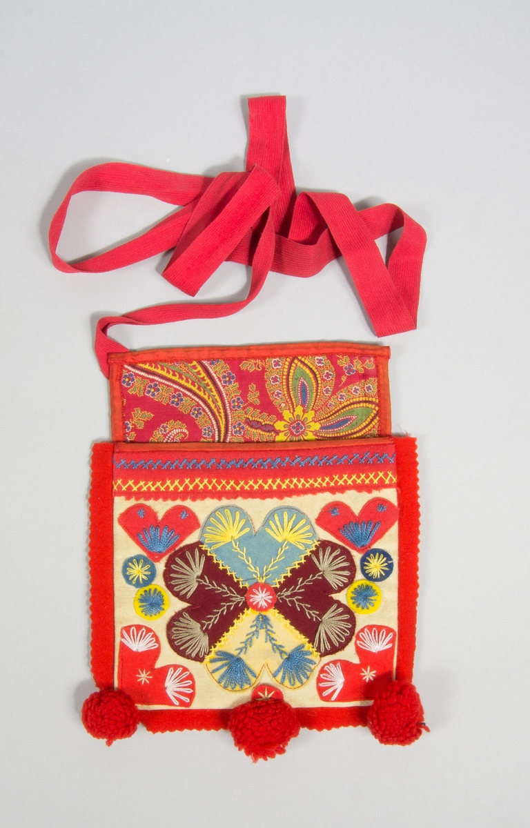 Kjolsäck till dräkt för kvinna från Rättviks socken, Dalarna. Modell med avskuret framstycke. Tillverkad av beige fabriksvävt bomullstyg, satin, med applikationer av tyger i blandade färger och kvalitéer, fastsydda med maskinsöm i rött. Centralt placerad hjärtblomma med småhjärtan i hörnen och utfyllande rundlar. Broderi utfört med bomullsgarn i flera färger: flätsöm, kråkspark, öglestygn, sticksöm. Ovanför applikationen en remsa av rött kläde med taggkant och broderi. Framstycket fodrat med beige kypertvävt bomullstyg, köpt. Överstycke av bomullstyg med tryckt mönster i flera färger på röd botten, kypertvävt. Både fram- och överstyckets överkanter kantade med rött sidenband. En remsa rött kläde inlagd i sido- och bottensömmen. I bottensömmen sitter också tre bollar av rött ullgarn. Bakstycke av svart glansigt fabriksvävt bomullstyg, kypert, fodrat med grått madrasstyg, stjärnmönster. Axelband av röd bomull, diagonalvävt, med hake och hyska.
