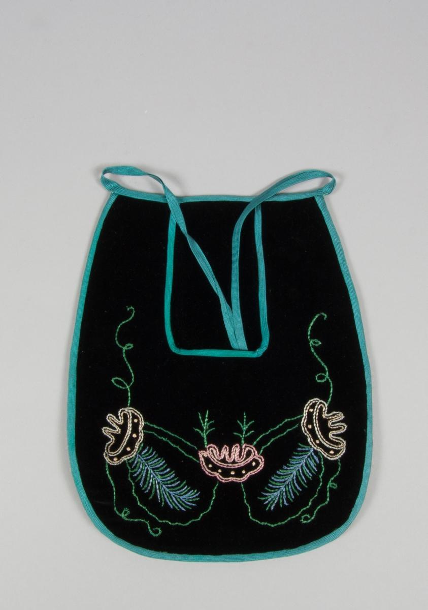 Kjolsäck till dräkt för kvinna från Hedemora, Dalarna. Modell med u-formad öppning. Tillverkad av svart bomullssammet, med broderi av glansigt garn i rosa, vitt, grönt och blått: kedjesöm. Motiv: blomformer med kvistar och slingor. Foder av grön sidentaft. Kantat runtom med blågrönt diagonalvävt konstsidenband. Sammet synligt även i öppningen. Bakstycke av svart sidensatin. Kantbandet har även använts till knytband i midjan.