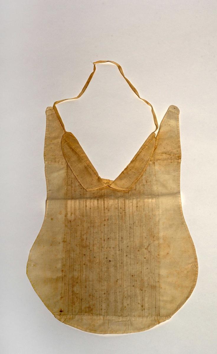 Skjortebrystet er eit avrunda tøystykke, med eit knapphol på kvar side. Øvst er det skøytt på eit skulderstykke, også med knapphol i enden. Rundt halsopninga er det sett på dobbel linning, som vert knytt saman i nakken.
