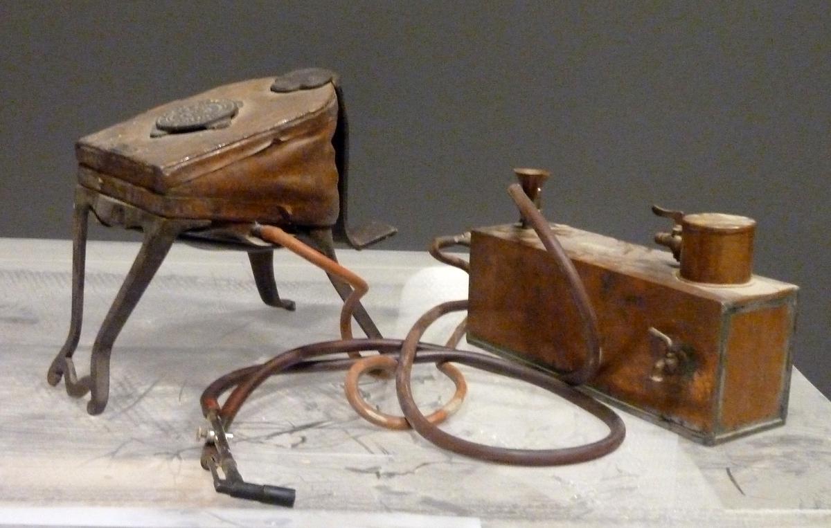 Loddepistol med belg og tank, separate og med slange til pistolen. Belgen har pedal i bakre kant. Tanken er av kopar og er rektangulær med to tappekraner og ei påfyllingstrakt.
