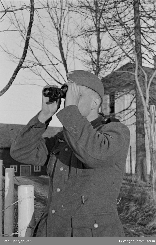 Soldat observerer med kikkert