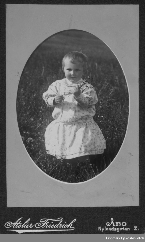 Fotografi av den lille piken Maila Marianne Gunnari i blomstereng