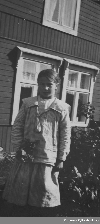 Fotografi av Aino Gunnari i hagen foran familien Gunnaris hus.ca.1922.