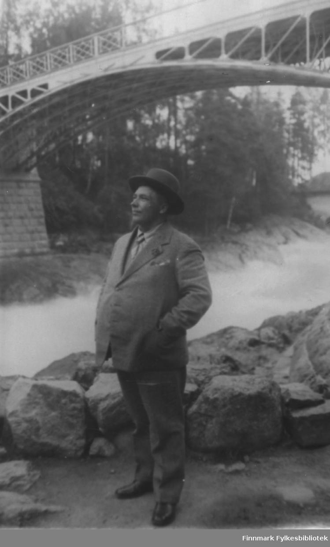 Enok Gunnari fotografert foran en bro, ca. 1930. Han er på reise i Finland