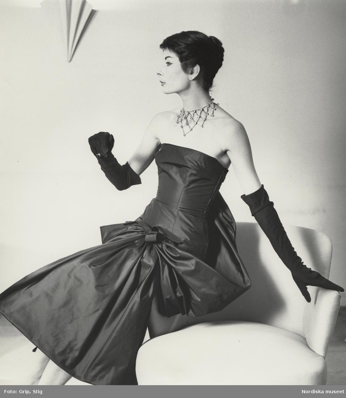 7f811037c62 Modell i axelbandslös aftonklänning, aftonhandskar och halsband. NK efter  Givenchy.