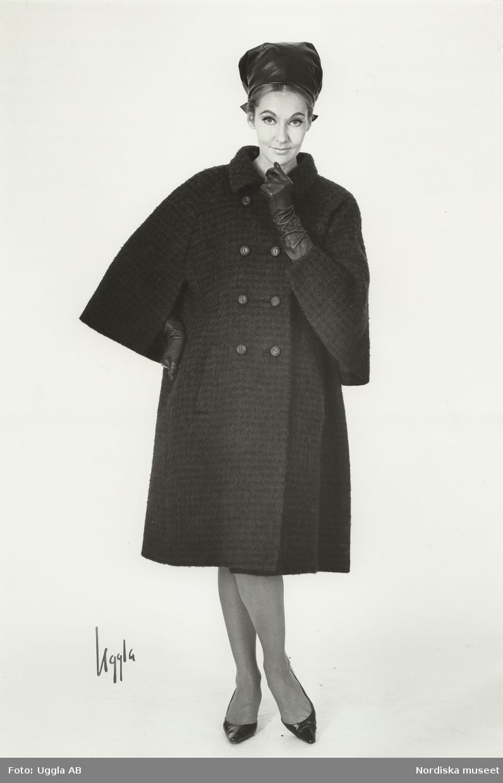 Modell i kappa i brunsvart tweed med dubbelknäppning. Sjalett i skinn och  handskar. Original a03b7bc702604