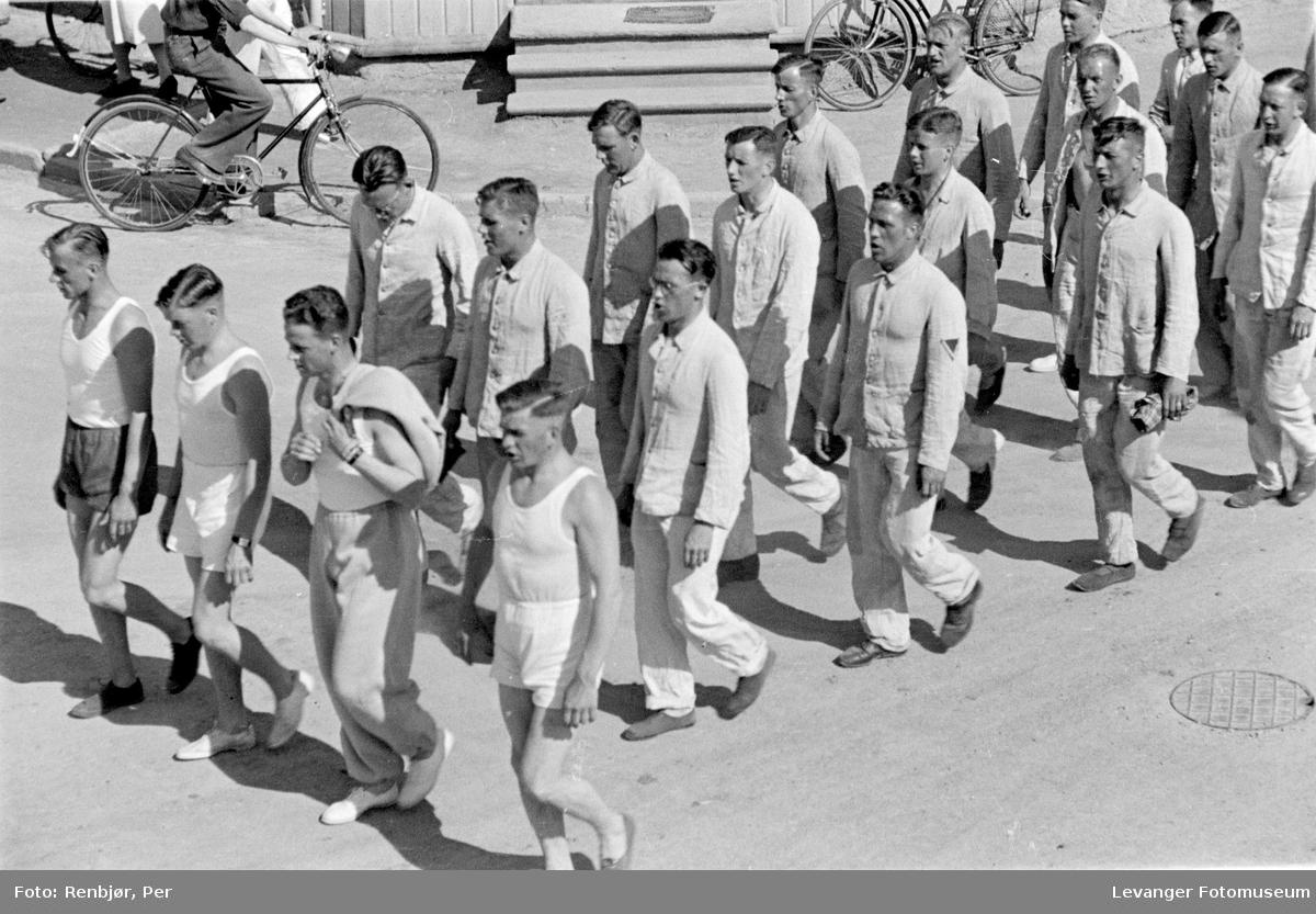 Syngende menn marsjerer i sluttet orden i sivil, trolig tyske soldater.