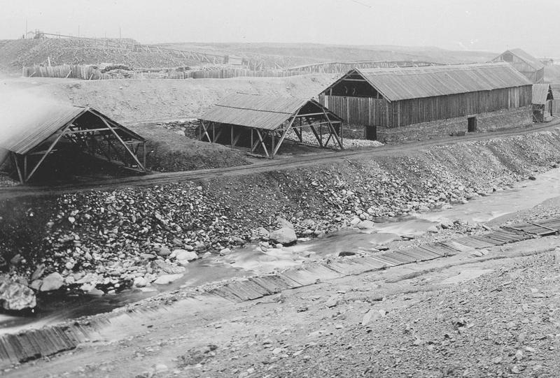 Bildet er tatt på slutten av 1800-tallet og viser kaldrøstene og murhytta. Murhytta har åpent møne slik at røyken fra kaldrøstinga skulle komme ut der.