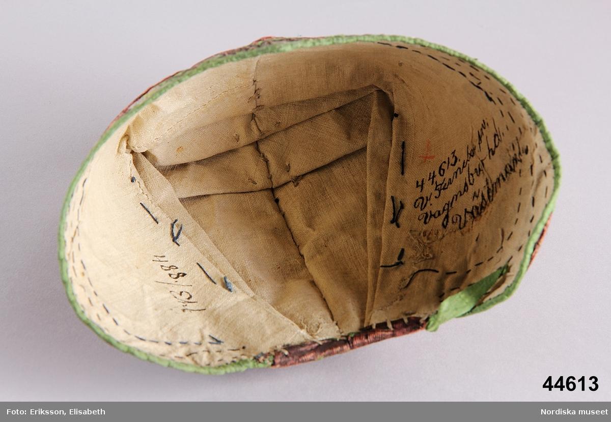 """Katalogkort: """" Högmössa af blommigt siden med väfda mönster. Halfstyf med grön sidenkant, snibb i pannan och två veck i hvardera sidan. Foder af hvit linneväf. Å mösstyget en slät enfärgad bård"""" /P.G.Vistrand/"""