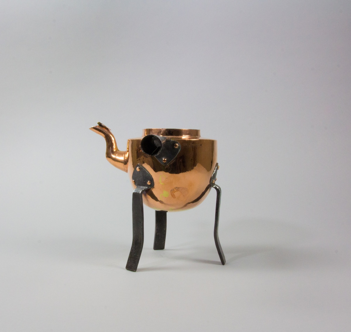 Kaffepanna tillverkad av koppar. Svängd pip med lövformat lock. Förtent insida. Handtag av järn, bockat för en förlängning av trä. Tre svagt svängda ben av järn med hjärtformade fästen nitade mot pannan. Med stämplar.