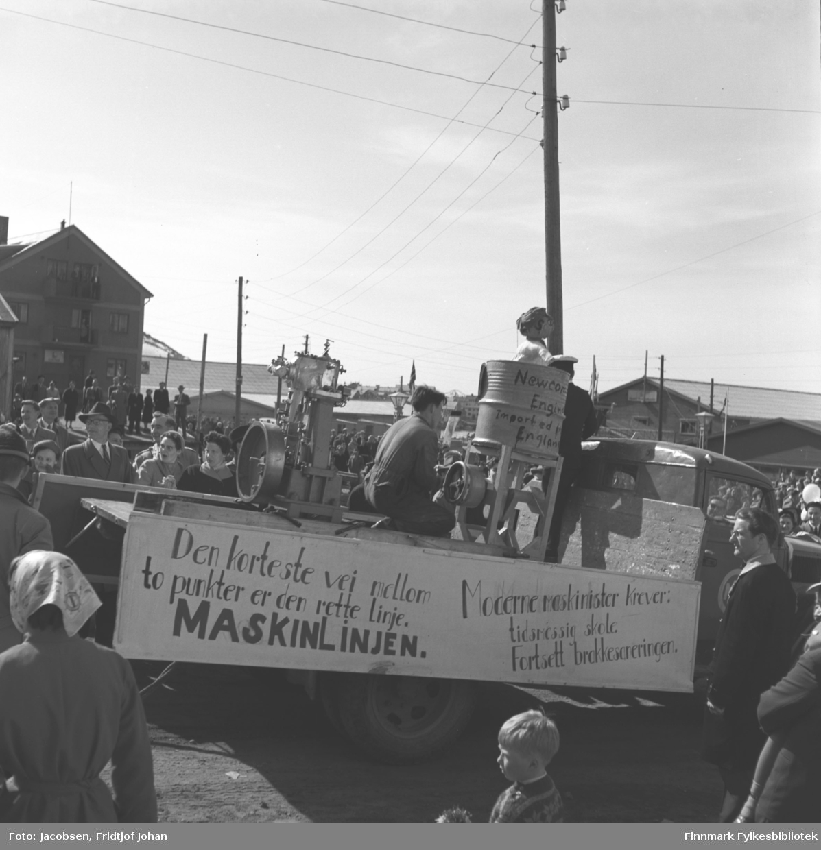 17. mai-feiring i Hammerfest. Bildet viser elever fra maskinlinjen ved Hammerfest yrkesskole og flere festkledt mennesker passere Hauans snekkerverksted. Husene øverst i bildet er Hamran.