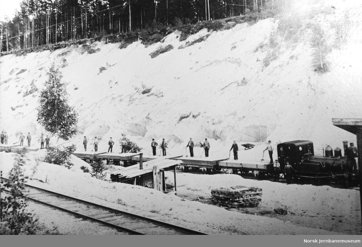 """Damplokomotivet nr 4 """"Harald"""" med grusvogner i grustak"""