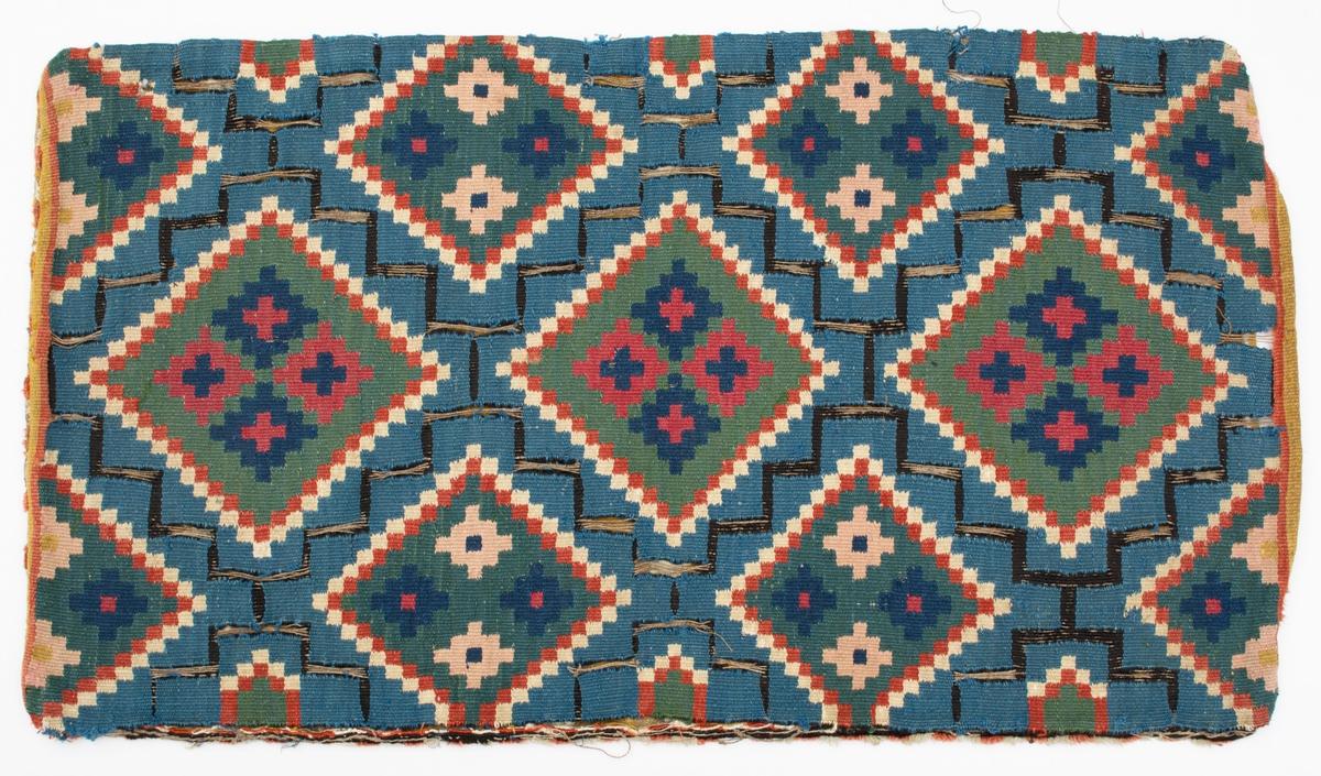 """Åkdyna vävd i rölakan (helstygn). Blå botten med svart gallerverk. Ytmönster av rutor inskrivna i romber med grön botten. Färger: Blå, grön, gulröd, blåröd, rosa, naturvit och gul. Varp i oblekt 2-trådigt s-tvinnat lingarn, 4 trådar/cm. Inslag i 2-trådigt z-tvinnat ullgarn, ca 22 trådar/cm, samt svart 1-trådigt ullgarn. Randig baksida vävd i inslagsrips och tvist i olika nyanser gult samt brungult, naturvitt och blekrosa. Samma kvalitet som i framsidan. Öppning (310 mm) i ena kortsidan som fållats med lingarn och försetts med en liten mässingshake. Rester av kavelfrans i rött och vitt runt om dynan. Rester av stoppning av dun. Märkt med påsydd tyglapp med texten: """"A. N° 101 Landstinget.  Torna h-d."""""""